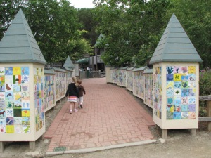 The entire playground is boxed in on all sides, to keep the little ones from escaping. The gateway is made up of ceramic tiles painted by the children who were responsible for the park's creative input.