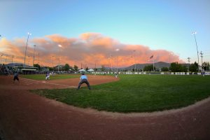 Photo by Ron Harpin/ www.rahphotosnv.com Smoke from the Bison Fire rises in the background at Governor's Field in Carson City during Carson Valley's semifinal win last night.