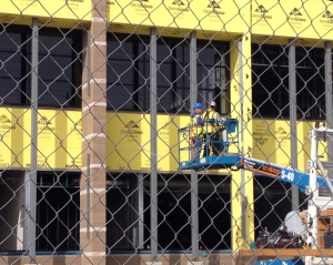 Workers install windows on the new STEM building at Douglas High School.